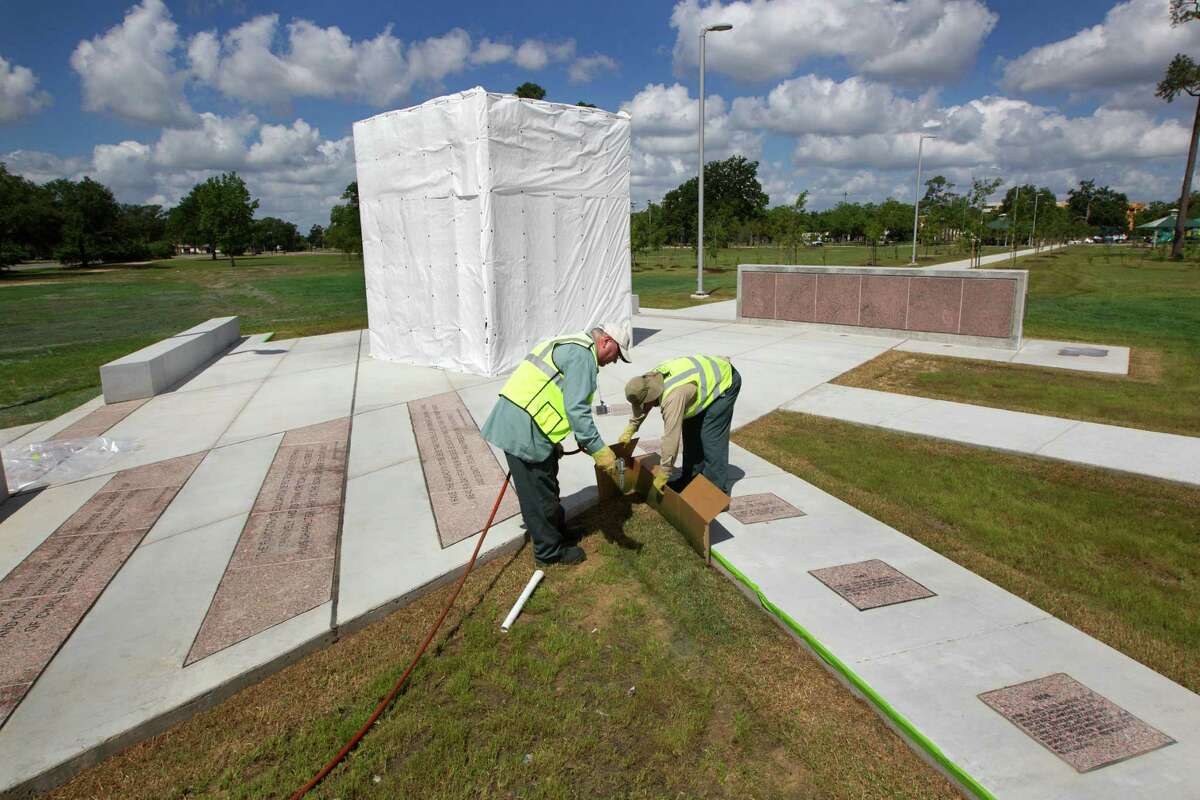 Houston Parks and Recreation employees James Carter, left, and Omero Campos put the finishing touches on the plaza with the new Martin Luther King Jr. statue.