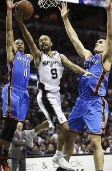 Tony Parker splits the defense of Russell Westbrook and Steven Adams (12) as the Spurs play the Thunder in the opener of the NBA Western Conference finals at the AT&T Center on May 19, 2014. Photo: Tom Reel, San Antonio Express-News