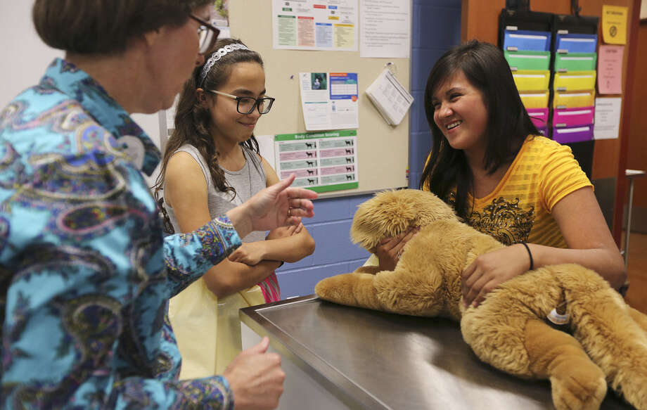 Dr. Fonzie Quance-Fitch (left) teaches sixth-graders Miranda Rodriguez (center) and Brenda Gomez how to properly restrain a dog during a vet tech school tour at Palo Alto College. Photo: Jerry Lara / San Antonio Express-News / ©2014 San Antonio Express-News