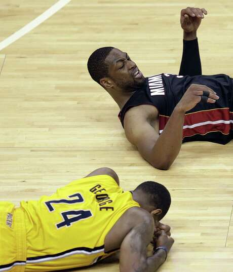 Indiana's Paul George lies on the floor after being hit in the head by the knee of Miami's Dwyane Wade in Game 2. George has a concussion. Photo: AJ Mast / Associated Press / FR123854 AP