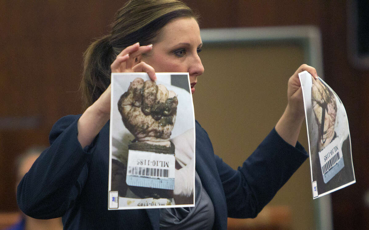 Prosecutor Donna Logan holds up evidence photos as she gives her closing arguments in the case against Narjes Modarresi.