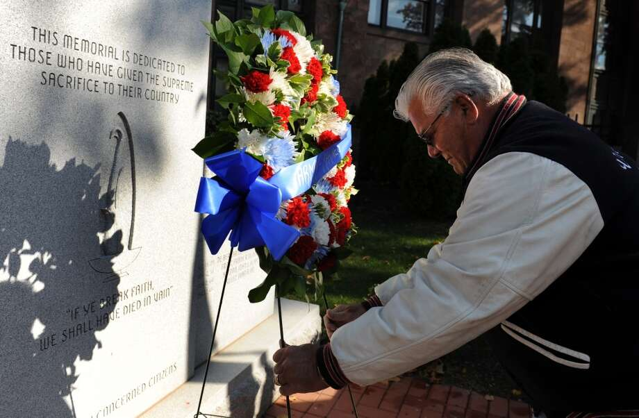 Army and Marine veteran Frank Somohano, of Milford, places a wreath in front of the Vietnam War monument during the Veterans Day Ceremony Friday, Nov. 11, 2011 at the Col. Mucci Memorial Green located on McLevy Green in Bridgeport, Conn. Col. Mucci, a Bridgeport native, led a force that rescued over 500 prisoners of war from a Japanese camp during World War Two. Photo: Autumn Driscoll