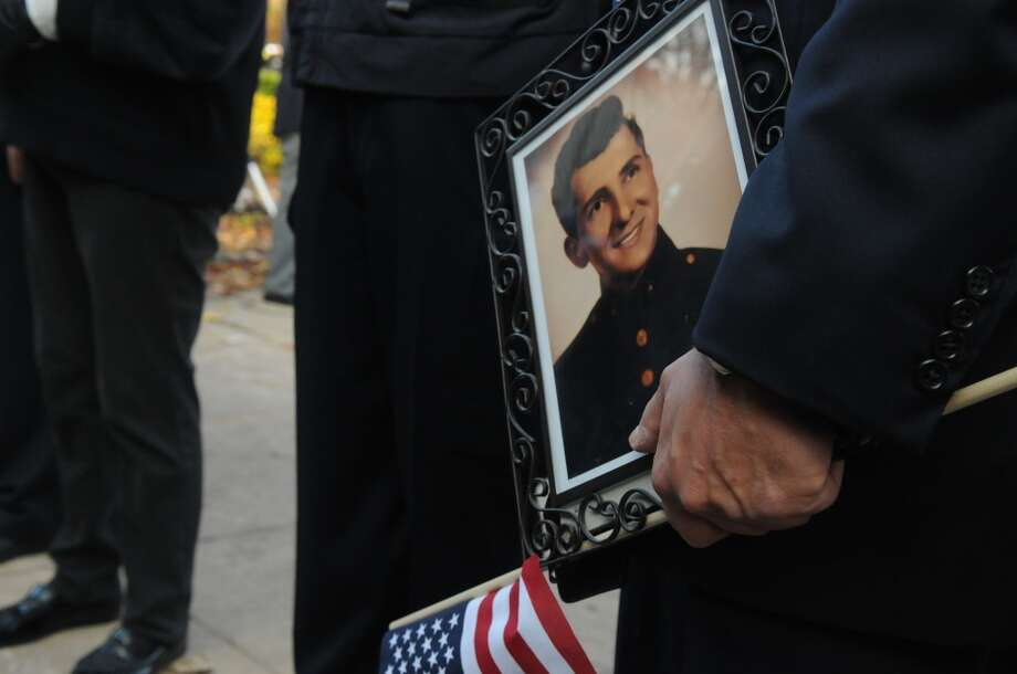 Representative Fred Camillo holds a photograph of his father Al Camillo, a Marine Corps drill instructor during the Korean War, as the Greenwich American Legion hosts a Veteran's Day ceremony at the war monument on Greenwich Avenue in Greenwich, Conn., Nov. 11, 2013. Photo: Keelin Daly, Contributed