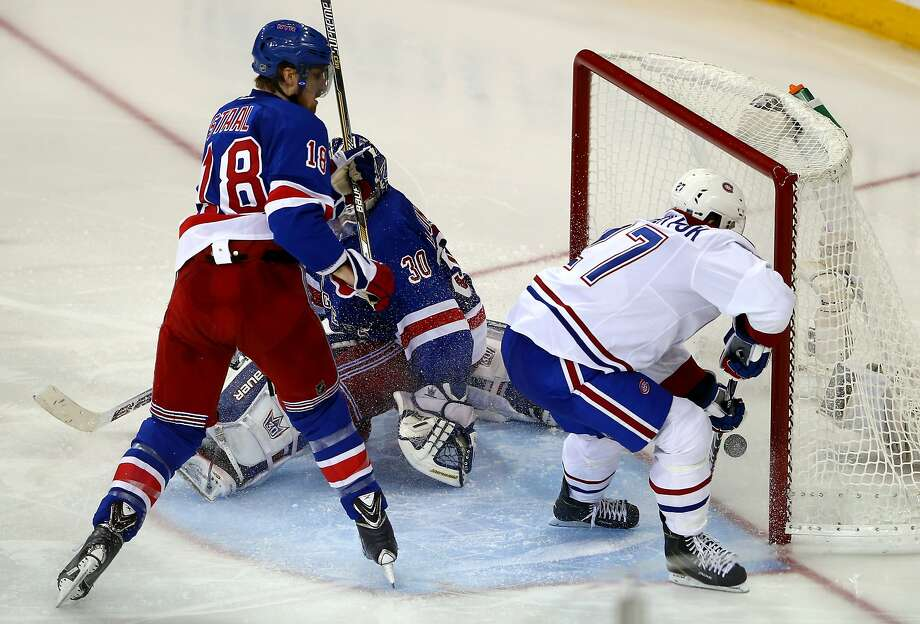 Alex Galchenyuk scores 1:12 into overtime to give the Canadiens their first win of the Eastern Conference finals. Goalie Henrik Lundqvist and defenseman Marc Staal can't save the Rangers. Photo: Elsa, Getty Images