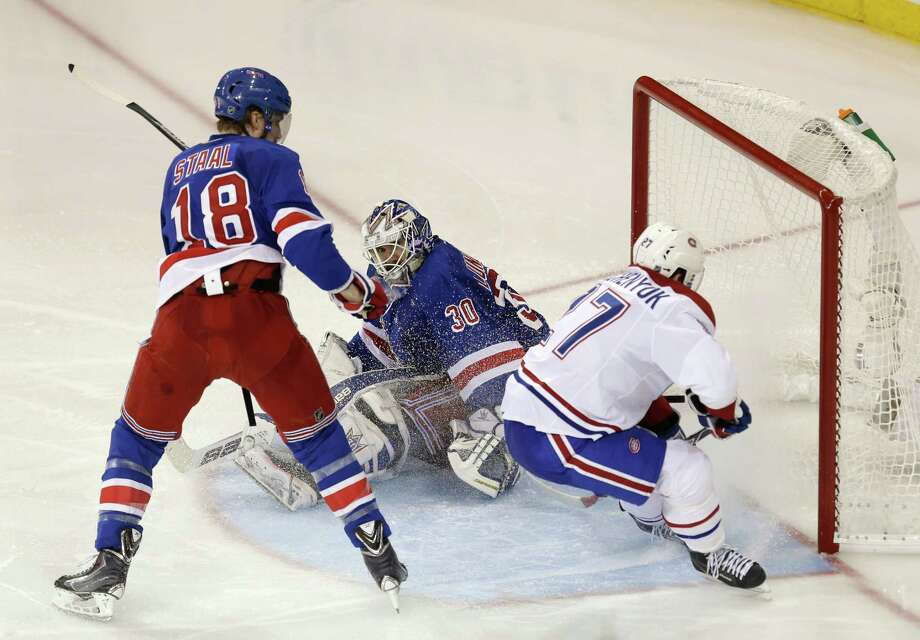 Montreal Canadiens' Alex Galchenyuk, right, scores past New York Rangers goalie Henrik Lundqvist and Rangers' Marc Staal, left, during overtime of Game 3 of the NHL hockey Stanley Cup playoffs Eastern Conference finals, Thursday, May 22, 2014, in New York. The Canadiens won 3-2. (AP Photo/Seth Wenig) ORG XMIT: NYSW112 Photo: Seth Wenig / AP