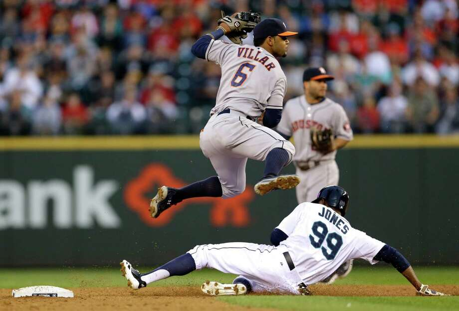 Astros shortstop Jonathan Villar goes over the top of the Mariners' James Jones in his bid to throw to first and complete a third-inning double play Thursday night. Photo: Ted S. Warren, STF / AP