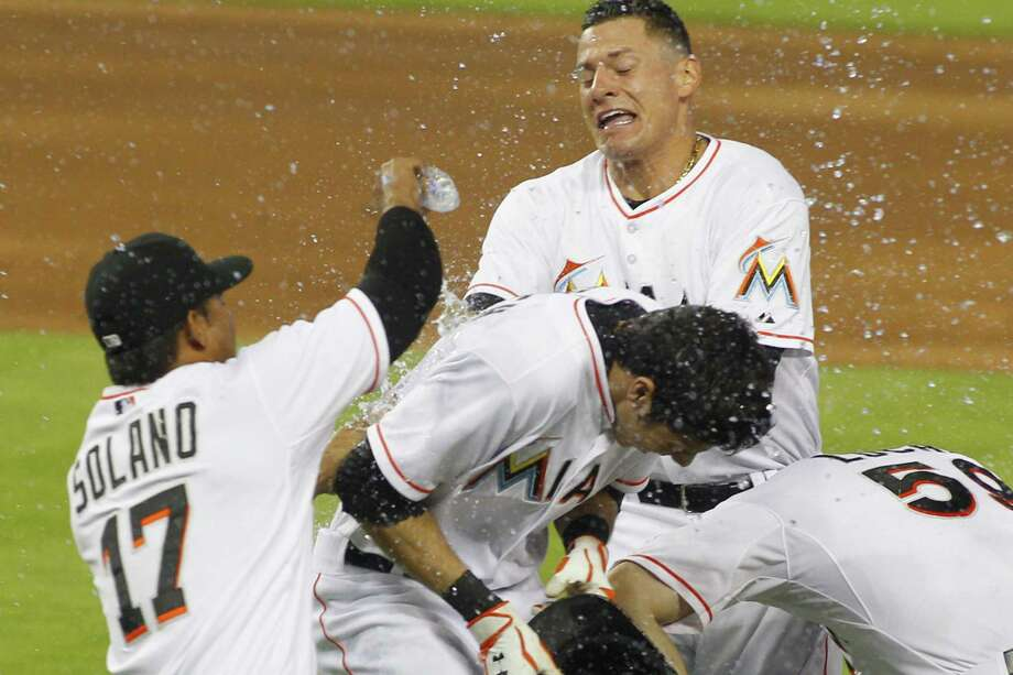 Miami's Christian Yelich (middle) is mobbed by teammates after his game-winning hit vs. Philly. Photo: Joe Skipper / Associated Press / FRE1711774 AP