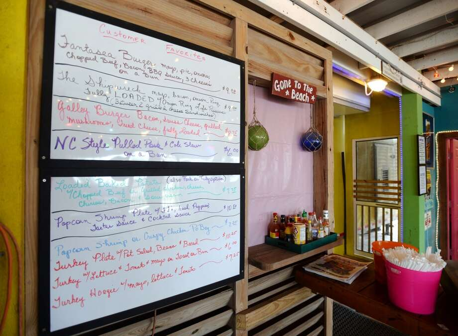 A whiteboard menu is displayed next to the entrance of FantaSea BBQ and Grill's kitchen, an attached food trailer. Crystal Beach and the Bolivar Peninsula is home to several quality restaurants and bars. Photo taken Saturday 5/10/14 Jake Daniels/@JakeD_in_SETX