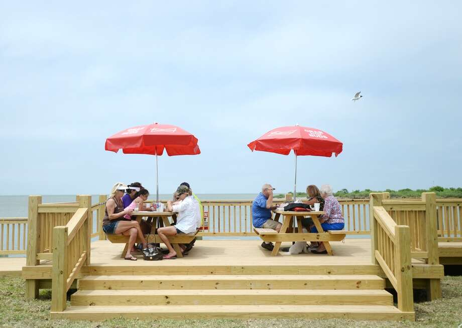 Down Under patrons eat at some of the covered, canal-side picnic tables Saturday afternoon. Crystal Beach and the Bolivar Peninsula is home to several quality restaurants and bars. Photo taken Saturday 5/10/14 Jake Daniels/@JakeD_in_SETX