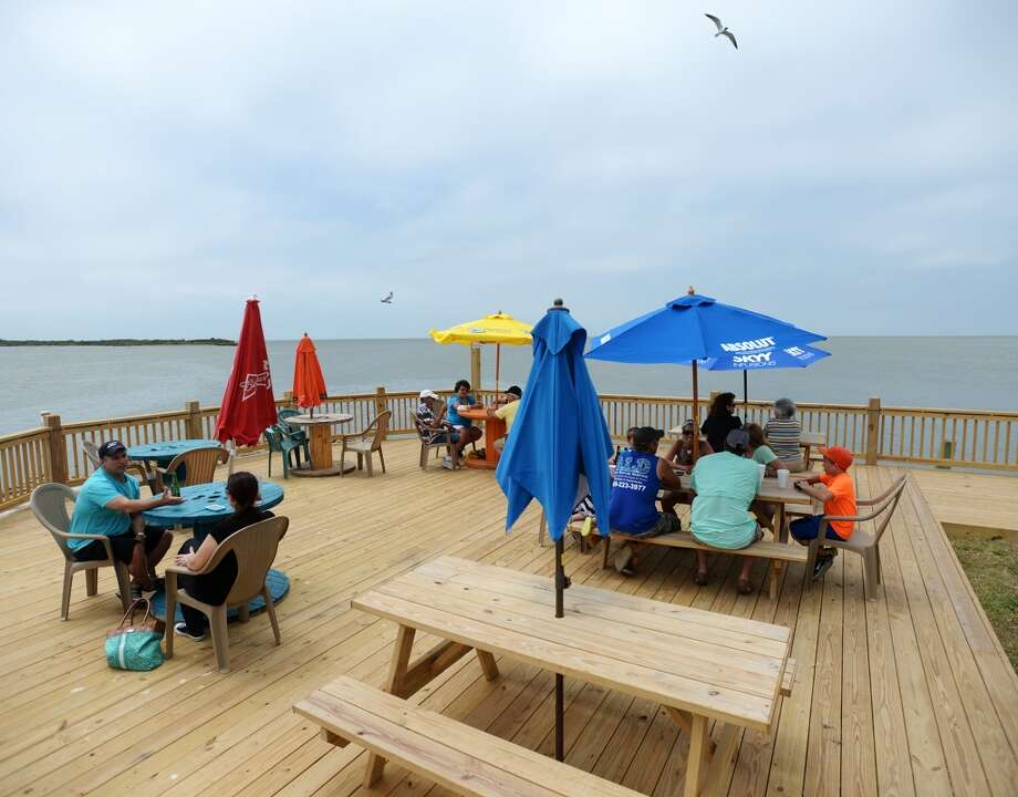 Patrons eat on the new deck at the Down Under Bar and Grill on Saturday afternoon. Crystal Beach and the Bolivar Peninsula is home to several quality restaurants and bars. Photo taken Saturday 5/10/14 Jake Daniels/@JakeD_in_SETX