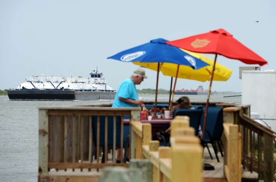 Barges motor past Stingaree Marina and diners at the Down Under Bar and Grill on Saturday afternoon. Crystal Beach and the Bolivar Peninsula is home to several quality restaurants and bars. Photo taken Saturday 5/10/14 Jake Daniels/@JakeD_in_SETX