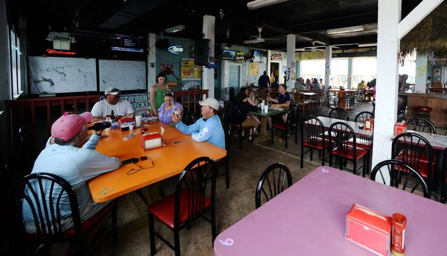 Patrons enjoy drinks and food in the shade at Down Under Bar and Grill on Saturday afternoon. Crystal Beach and the Bolivar Peninsula is home to several quality restaurants and bars. Photo taken Saturday 5/10/14 Jake Daniels/@JakeD_in_SETX