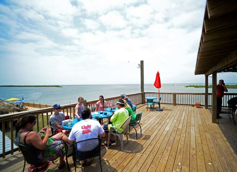 Diners sit out in the sun on the deck of the Stingaree Marina Restaurant on Saturday afternoon. Crystal Beach and the Bolivar Peninsula is home to several quality restaurants and bars. Photo taken Saturday 5/10/14 Jake Daniels/@JakeD_in_SETX