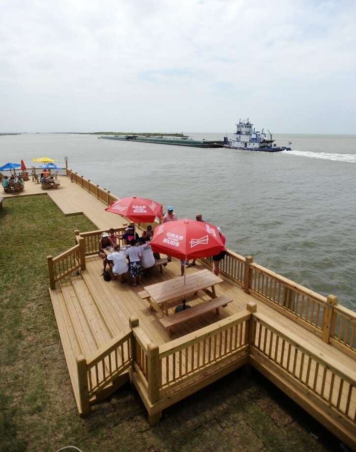 A barge passes by outdoor diners at Stingaree Marina Restaurant and the Down Under Bar and Grill on Saturday afternoon. Crystal Beach and the Bolivar Peninsula is home to several quality restaurants and bars. Photo taken Saturday 5/10/14 Jake Daniels/@JakeD_in_SETX