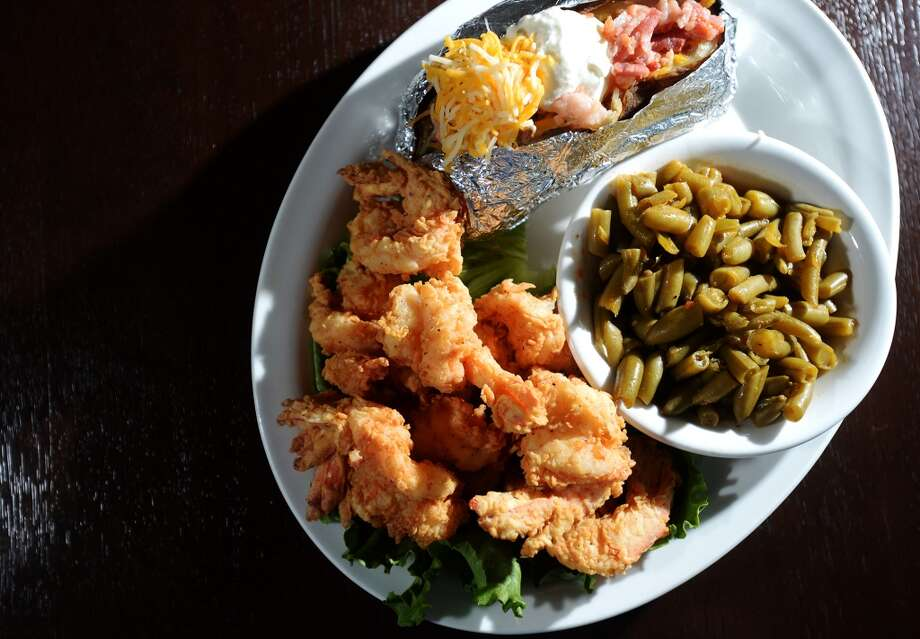 Pictured is a plate of fried shrimp, a loaded baked potato, and green beans, all from the kitchen of Steve's Landing. Crystal Beach and the Bolivar Peninsula is home to several quality restaurants and bars. Photo taken Saturday 5/10/14 Jake Daniels/@JakeD_in_SETX