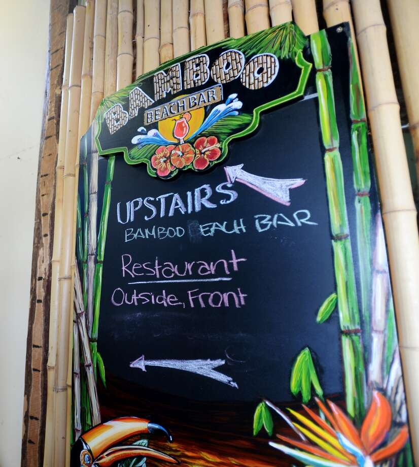 A sign points upstairs to the Bamboo Beach Bar, which resides above Barefoot Bill's American Grill. Crystal Beach and the Bolivar Peninsula is home to several quality restaurants and bars. Photo taken Saturday 5/10/14 Jake Daniels/@JakeD_in_SETX