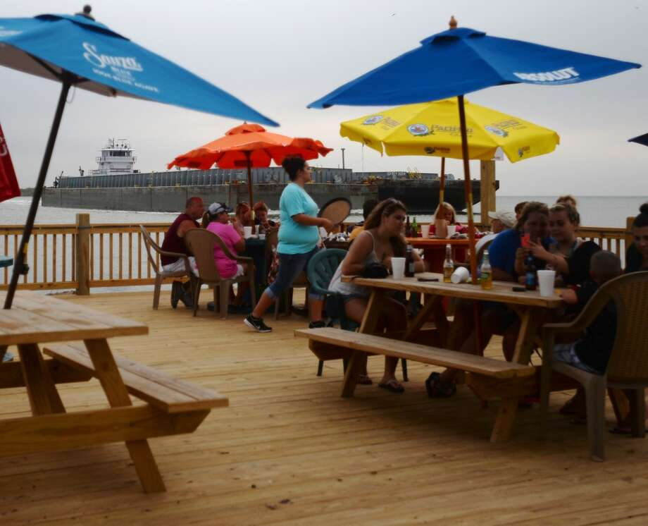 Diners relax on the Down Under Bar and Grill's new deck as barges float by Saturday afternoon. Crystal Beach and the Bolivar Peninsula is home to several quality restaurants and bars. Photo taken Saturday 5/10/14 Jake Daniels/@JakeD_in_SETX