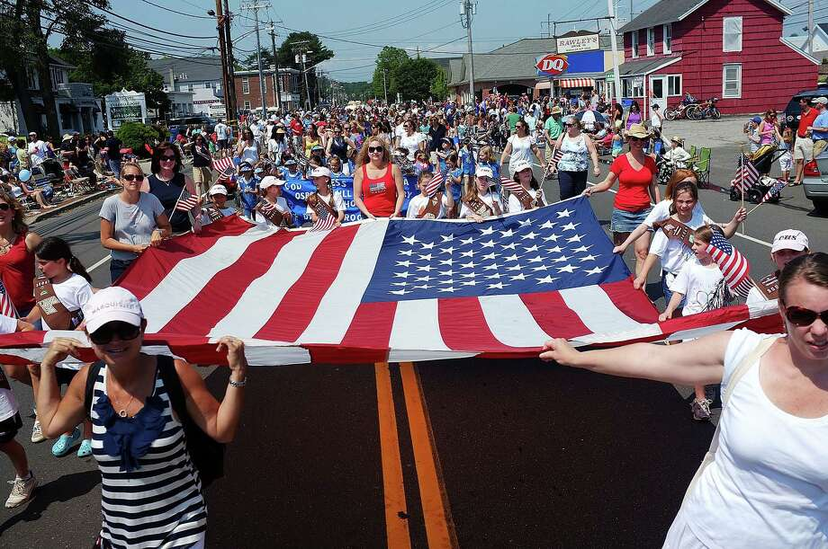 "A group of marchers carries a large American flag down Post Road in the town's 2012 Memorial Day parade. Fairfield Citizen columnist Patricia A. Hines writes of the annual event: ""In the years after my father died and Mom was still able, I took her to the Fairfield Memorial Day parade. We parked ourselves on beach chairs in a prime location in Fairfield Center. She loved our parade ó and why not? Itís one of the best in the area. And this yearís is bound to be even better, considering the town is celebrating its 375th anniversary."" Photo: Getty Images / Spencer Platt / Fairfield Citizen"