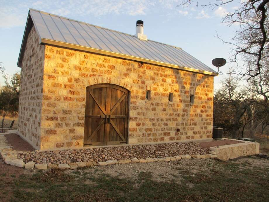 From the back (or the first side you see when you approach this rental property), the Coyote Cabin looks like a stone barn. But walk around to the front and a wide porch with big double doors to a modern, luxurious cabin awaits visitors. Photo: Terry Scott Bertling, San Antonio Express-News