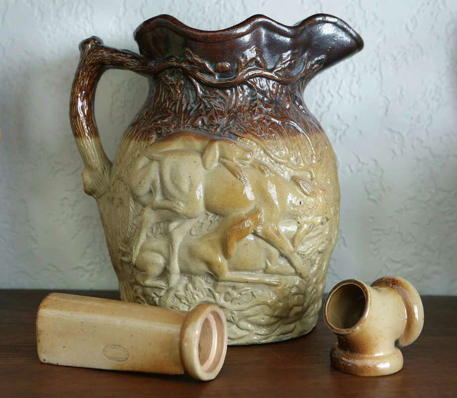 A Doulton Watts Lambeth Pottery pitcher with a hunting scene is part of the collection in the home of Ann and George Berg.  The pieces in front are small sales samples of pipes that were used underground in London. Photo: BOB OWEN, San Antonio Express-News / © 2012 San Antonio Express-News