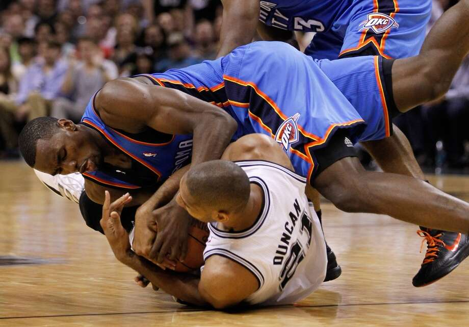 Serge Ibaka #9 of the Oklahoma City Thunder and Tim Duncan #21 of the San Antonio Spurs battle for the ball on the floor in the second quarter in Game Two of the Western Conference Finals of the 2012 NBA Playoffs at AT&T Center on May 29, 2012 in San Antonio, Texas. NOTE TO USER: User expressly acknowledges and agrees that, by downloading and or using this photograph, user is consenting to the terms and conditions of the Getty Images License Agreement.  (Photo by Tom Pennington/Getty Images) Photo: Getty Images