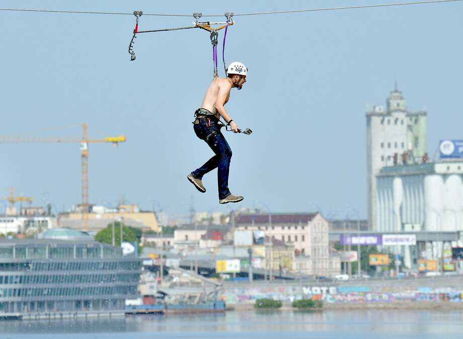 This is the last time I forget my harness:A man hung by the skin of his back crosses the Dniper River on a 552-meter-long cable stretching between the two banks in Kiev. No explanation for the painful feat was offered by the photographer. Photo: Sergei Supinsky, AFP/Getty Images