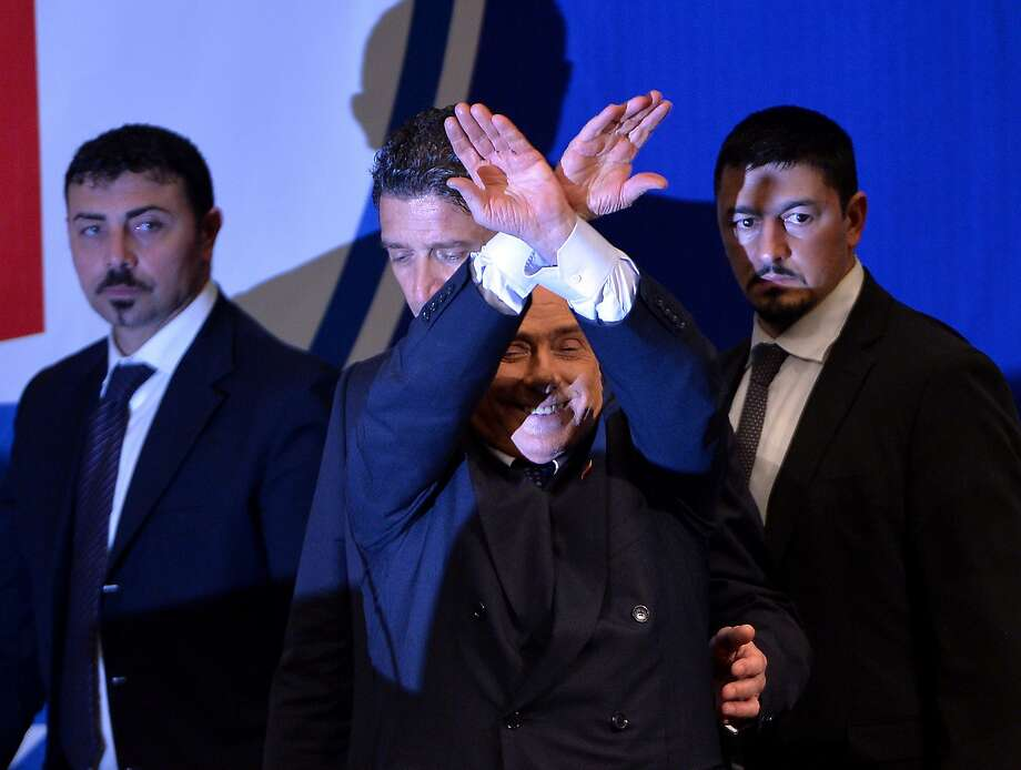 What exactly is Silvio Berlusconi doing with his hands? Signaling no goal? Surrendering to the authorities? Shadow puppets? No, the former Italian prime minister is pretending to be in handcuffs, an apparent 