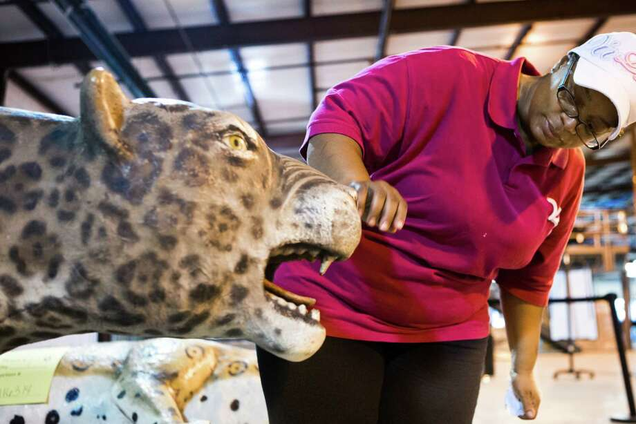Cassandra Dallas, 47, takes a look at the large Forest Brook High School mascot fiberglass statue at the  Houston Independent School District auction. Dallas who was a student at Forest Brook from 1980 through 1984 remembers the color guard parading the large Jaguar on the field every time their football team scored a touchdown.   Thursday, May 22, 2014, in Houston. Photo: Marie D. De Jesus, Houston Chronicle / © 2014 Houston Chronicle