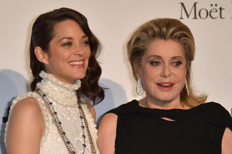 French actresses Marion Cotillard (L) and Catherine Deneuve pose as they arrive for the amfAR 21st Annual Cinema Against AIDS during the 67th Cannes Film Festival at Hotel du Cap-Eden-Roc in Cap d'Antibes, southern France. Photo: ALBERTO PIZZOLI, AFP/Getty Images