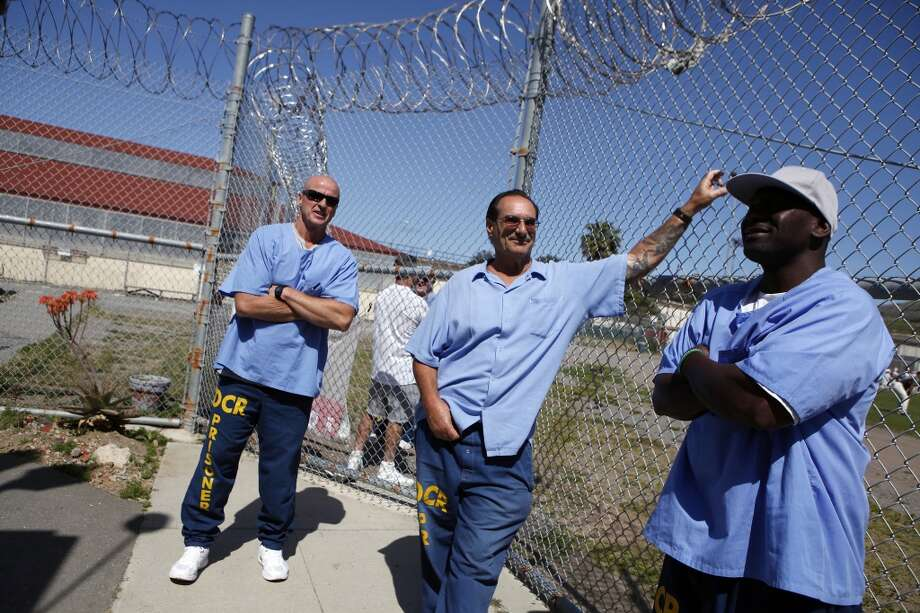 "(L-R)Inmates David ""Lumpy"" Stephens, David Basile and Vantrice Laster stand outside next to the yard as Cal Bears football players make a visit to San Quentin State Prison in San Quentin, CA, Saturday May 3, 2014. Photo: The Chronicle"