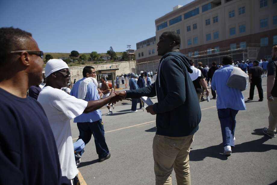 Defensive end Jonathan Johnson shakes hands with an inmate while walking through the yard as Cal Bears football players make a visit to San Quentin State Prison in San Quentin, CA, Saturday May 3, 2014. Photo: The Chronicle