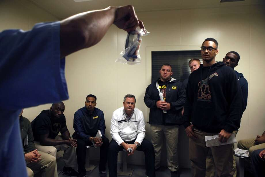 Cal Bears football players and staff including head coach Sonny Dykes, center, listen as inmate Miguel Quezada shows them a toiletries pack that inmates receive upon arrival to prison, during a  team visit to San Quentin State Prison in San Quentin, CA, Saturday May 3, 2014. Photo: The Chronicle