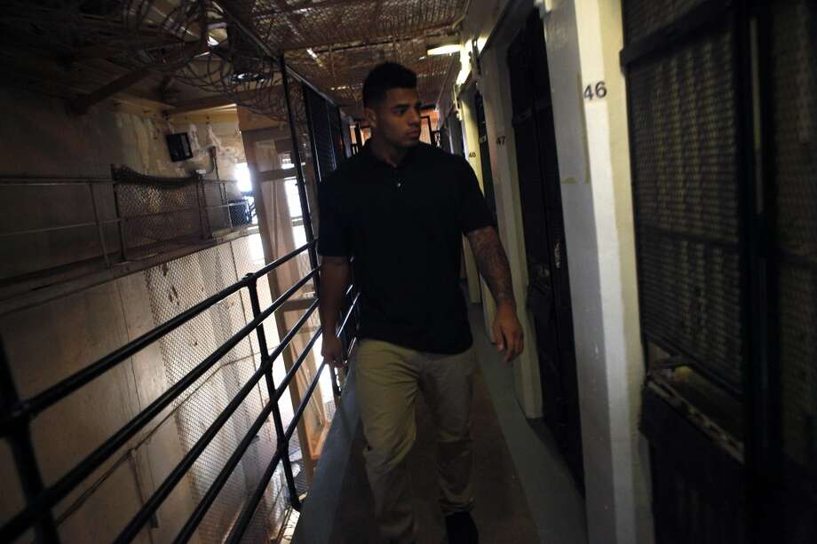 Linebacker Edward Tandy walks down a line of cells in a housing block as Cal Bears football players make a visit to San Quentin State Prison in San Quentin, CA, Saturday May 3, 2014. Photo: The Chronicle