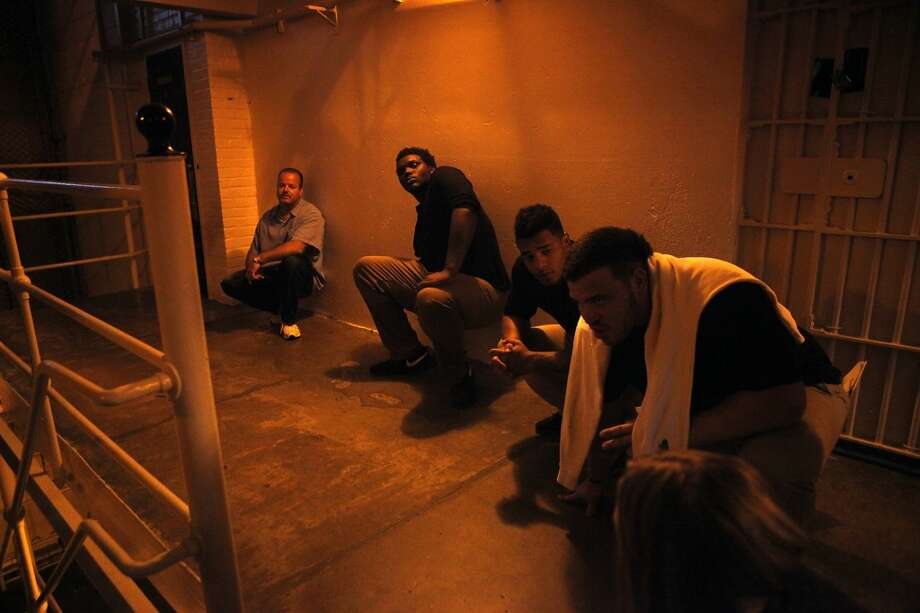Players, staff members and inmates must crouch down as a siren sounds inside a housing block as Cal Bears football players make a visit to San Quentin State Prison in San Quentin, CA, Saturday May 3, 2014. Photo: The Chronicle