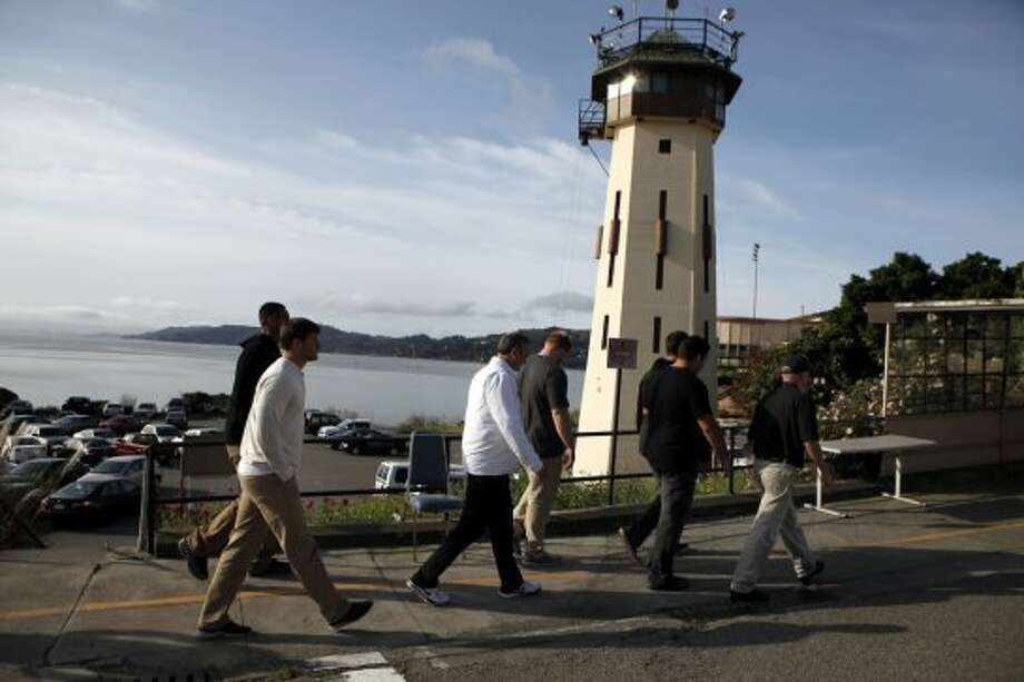 Cal Bears football players and staff members walk past a guard tower as they arrive for a visit to San Quentin State Prison in San Quentin, CA, Saturday May 3, 2014. Photo: The Chronicle