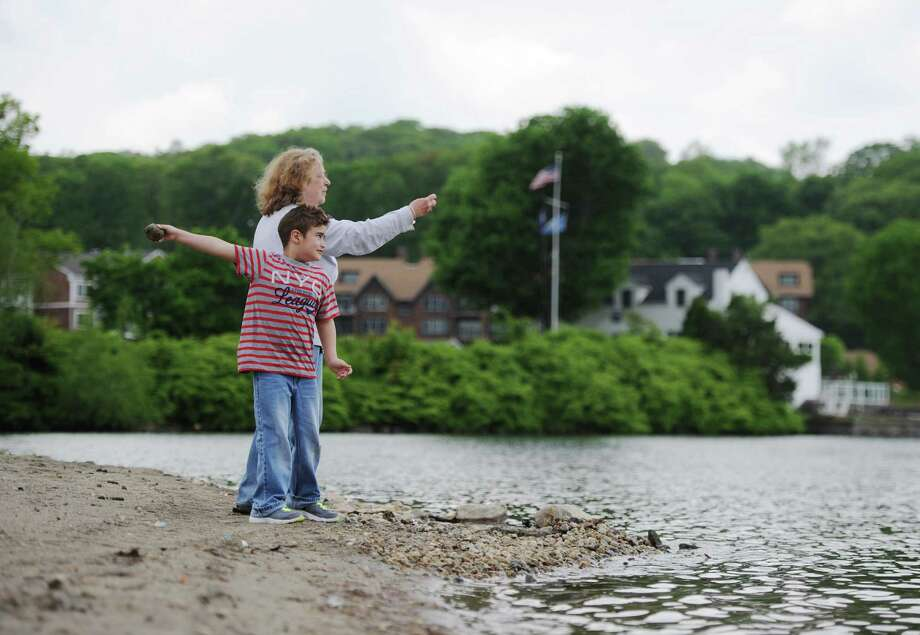 Mary Anne Stamets, of Danbury, and Cisco Bordoi, 6, throw stones into Candlewood Lake on the beach at Candlewood Town Park in Danbury, Conn. Friday, May 23, 2014.  Local beaches are cleaning up to prepare for visitors during beach season. Photo: Tyler Sizemore / The News-Times
