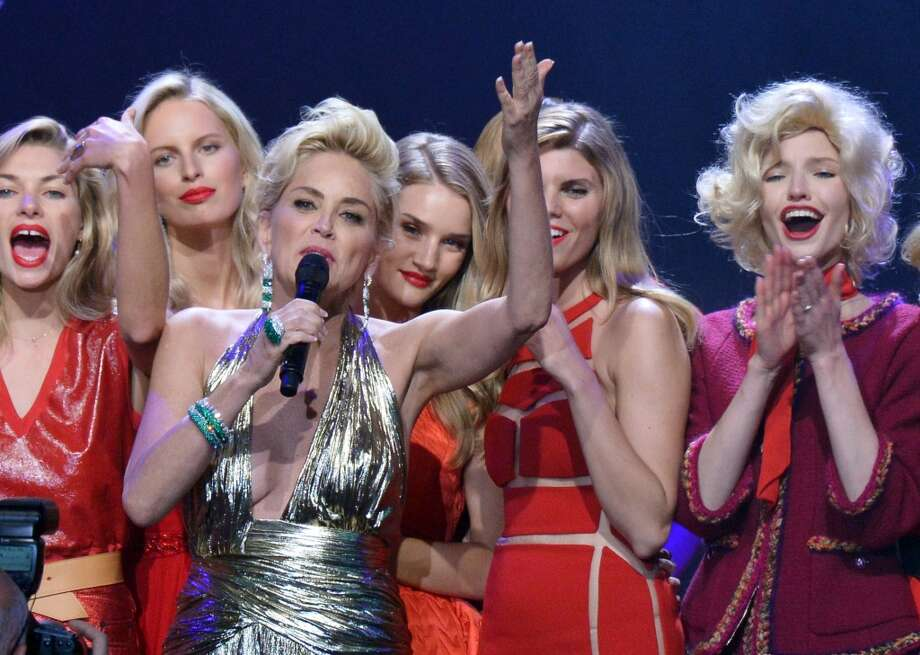 Actress Sharon Stone (front) conducts an auction with (back, from L) Australian model Jessica Hart, Czech model Karolina Kurkova, British model and actress Rosie Huntington-Whiteley, Belarussian model Maryna Linchuk and South Korean model Soo Joo Park during the amfAR 21st Annual Cinema Against AIDS on the sidelines of the 67th Cannes Film Festival at Hotel du Cap-Eden-Roc in Cap d'Antibes, southern France, on May 22, 2014. Photo: ALBERTO PIZZOLI, AFP/Getty Images