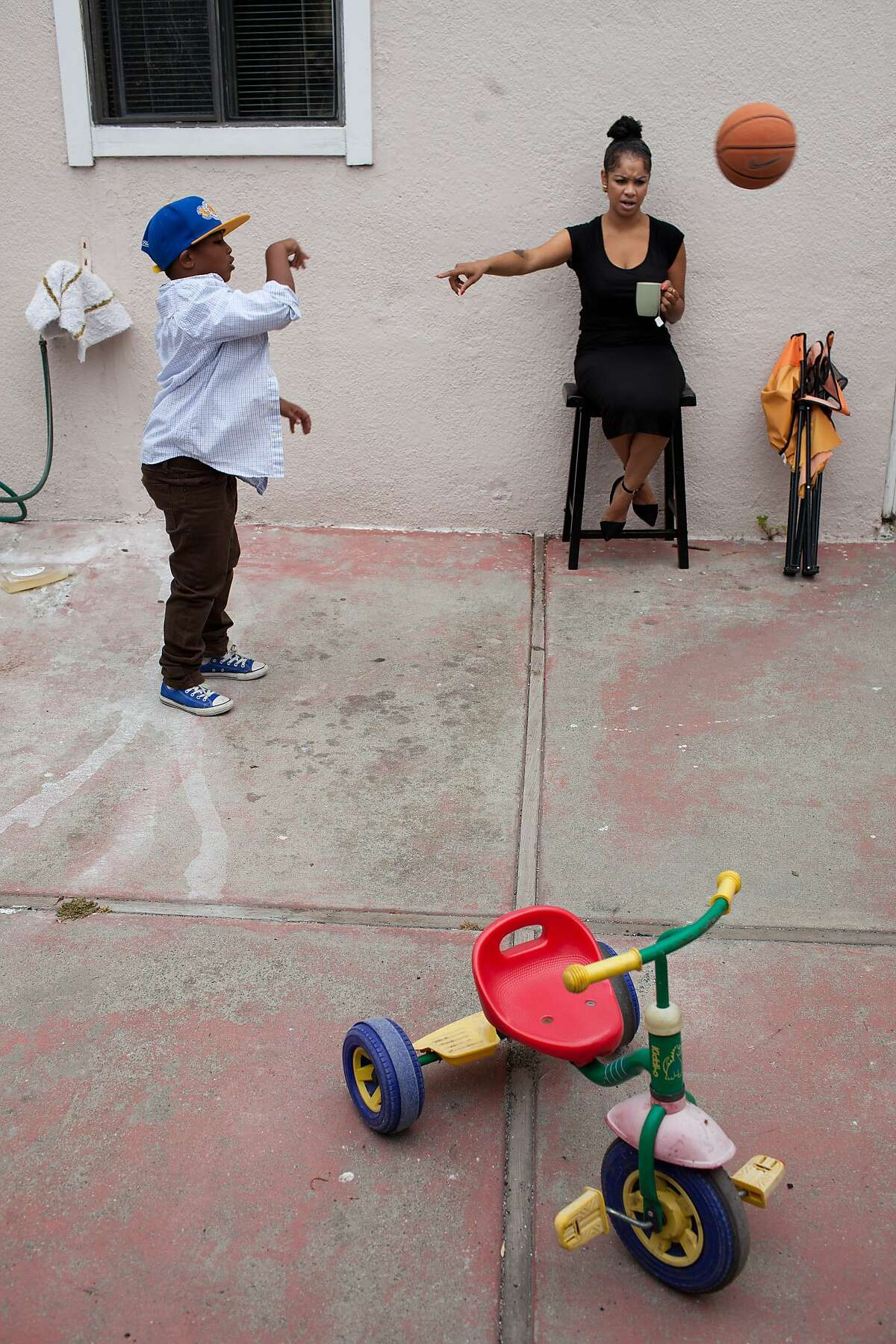 Essence Hope, 29, talks to her son Bryce, 6, as he plays basketball in the morning at their apartment in Oakland, Calif. on Friday, May 23, 2014. Hope has worked minimum wage jobs ever since she left high school.