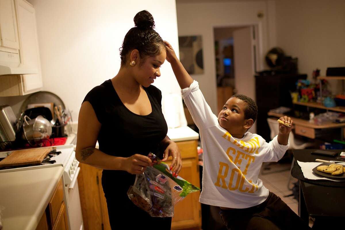 """Essence Hope, 29, left gets ready for the day with her son Bryce, 6, at her apartment in Oakland, Calif. on Friday, May 23, 2014. Hope has worked minimum wage jobs ever since she left high school. """"Through struggling I've learned about humility and ego. I have no ego because I have no money,"""" Hope said."""