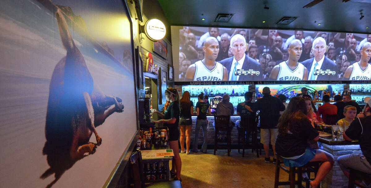 A lounging kangaroo graces the wall at the Australian-themed Roo Pub as Spurs Australian player Patty Mills confers with Gregg Popovich during game 2 of the Western Conferernce finals.