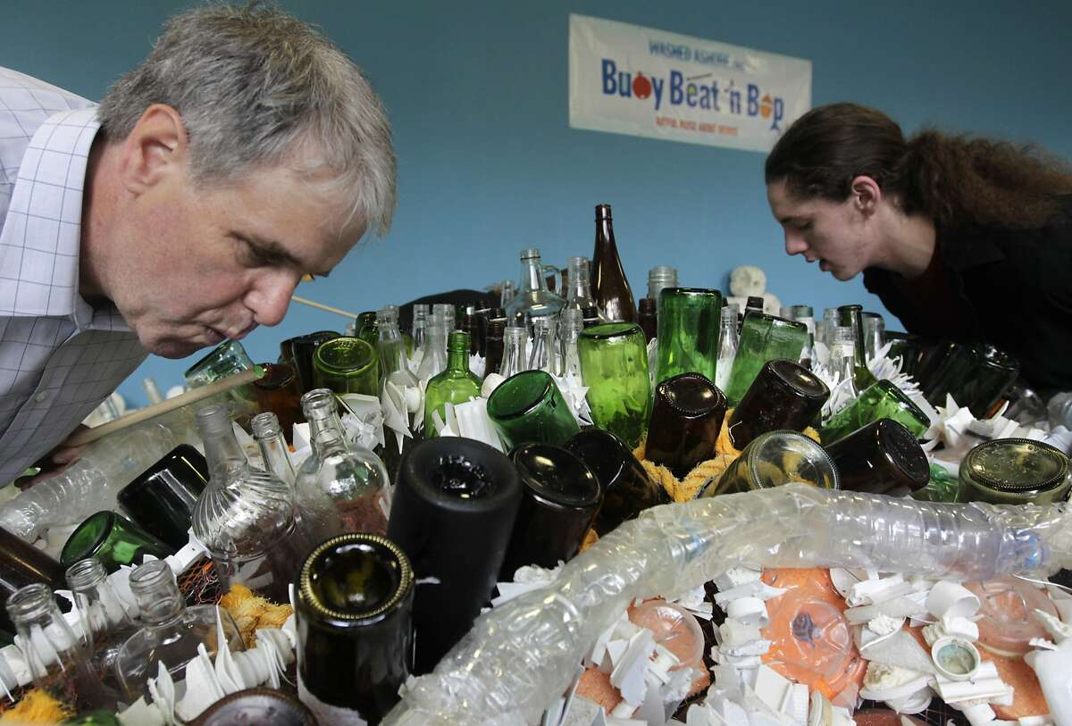 Anthony Pescatore (left) and Kevin Johnson blow into bottles at