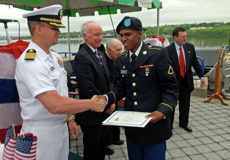 Anthony Benbow, 27, receives his certificate of citizenship during a special naturalization ceremony held in honor of Military Appreciation Month at the Submarine Force Museum in Groton, Conn. on Friday, May 23, 2014. Benbow, originally from Jamaica now lives in Bridgeport, Conn. Photo: Contributed Photo, William Larned/Contributed Photo / Connecticut Post Contributed