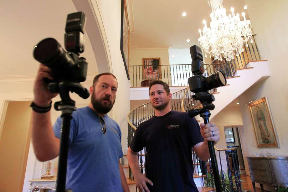 Real estate photographer Bill Krampitz shows some images to fellow photographer - and cousin - Tad Kramptiz, of TK Images, as they complete their job. Photo: Mayra Beltran, Staff / © 2014 Houston Chronicle
