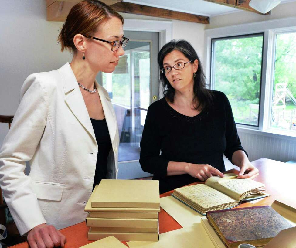 Historic Cherry Hill curator Deborah Emmans-Andarawis, left, picks up Van Rensselaer manuscript cook books from the 18th-20th centuries form Samantha Couture, a book binder who's restored them at her Stockade home studio Thursday May 15, 2014, in Schenectady, N.Y. (John Carl D'Annibale / Times Union)