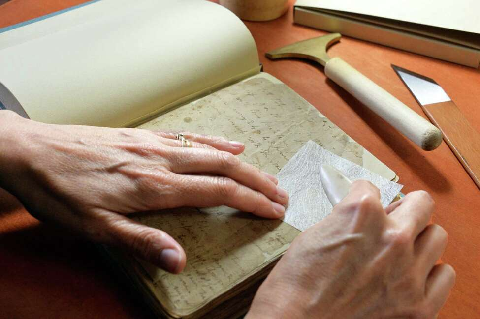 Book binder Samantha Couture restores an 18th C book from Historic Cherry Hill at her Stockade home studio Thursday, May 15, 2014, in Schenectady, N.Y. (John Carl D'Annibale / Times Union)