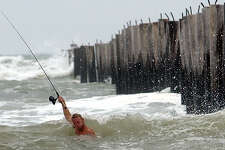 Dewayne Patten tries to keep his head above water as the waves crash around him while he surf fishes near the pier at J.P. Luby Surf Park Sunday, June 30, 2002, in Corpus Christi, Texas. (AP Photo/Corpus Christi Caller-Times, Michelle Christenson)