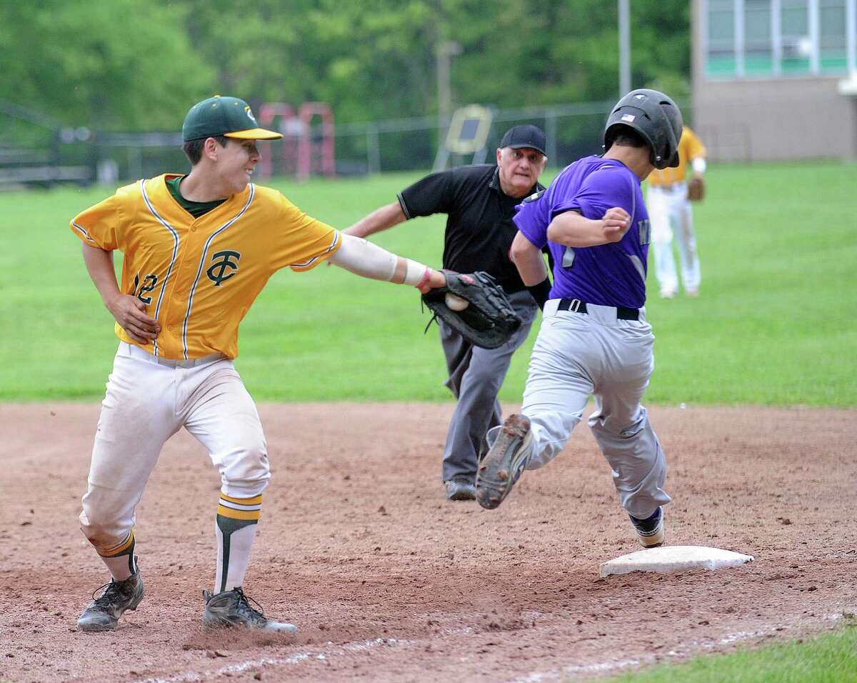 Westhill's Cameron Curto is safe at first base as Trinity Catholic's Jackson Solis reaches but misses the tag during Friday's baseball game at Trinity Catholic High School on Friday, May 23, 2014.