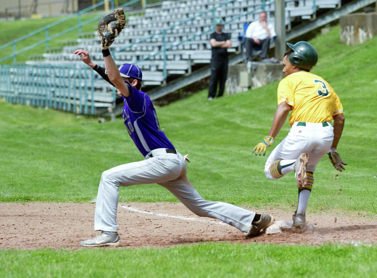 Trinity Catholic's Randy Polonia is safe at first base as Westhill's Matt Gorey catches the ball during Friday's baseball game at Trinity Catholic High School on Friday, May 23, 2014.