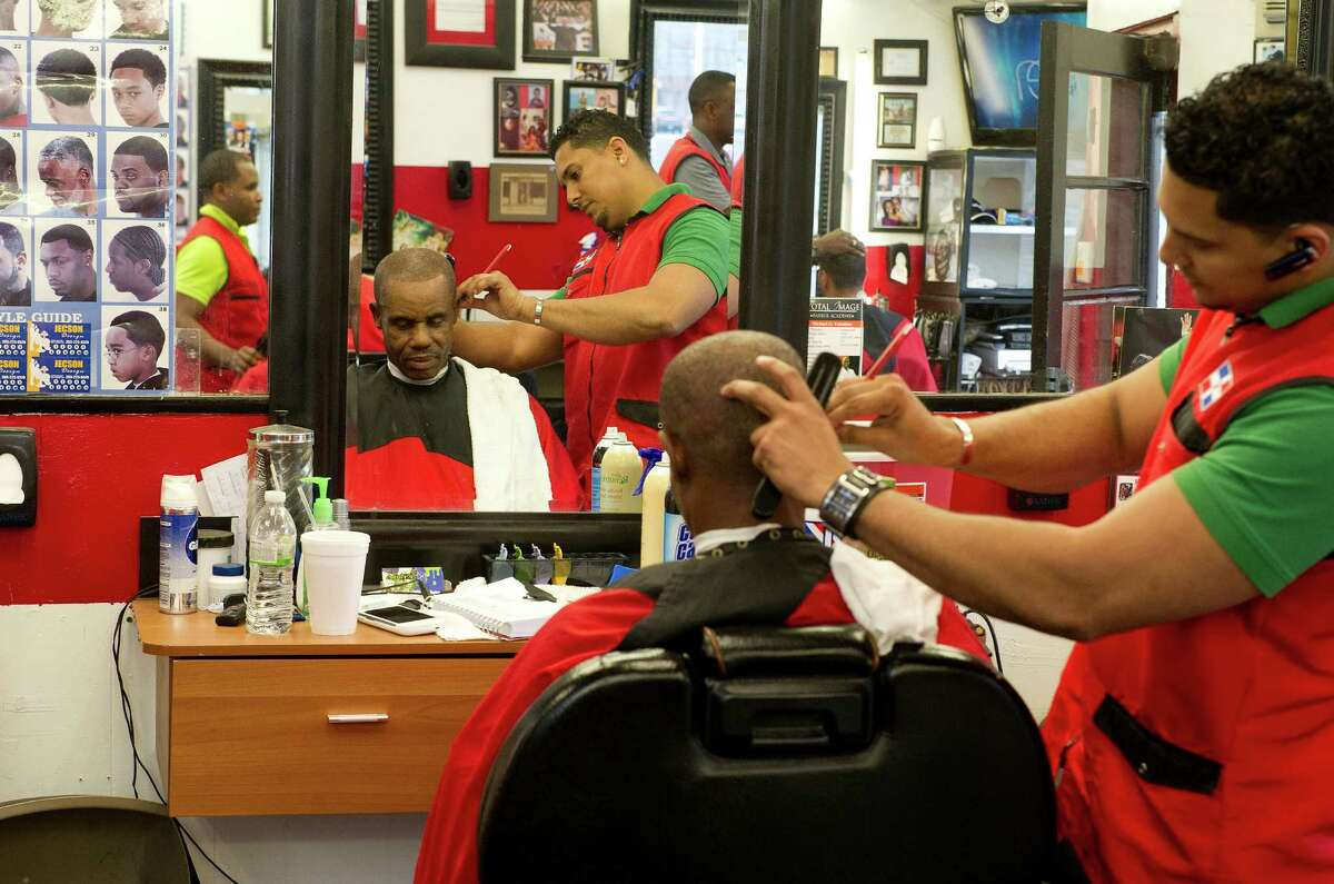 Lenin De La Cruz, who goes by Ariel, cuts Lambert Henry's hair at Love Cuts in Stamford, Conn., on Thursday, May 22, 2014. Ariel is a graduate of Mike Valentine's hairdressing school and is currently waiting to take the state certification test.