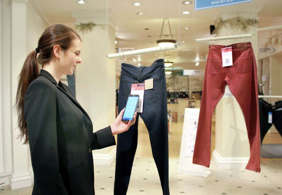 In this undated photo provided by Hointer, a woman demonstrates the Seattle store's shopping technology. Hointer displays clothing not in piles or on racks but as one piece hanging at a time, like a gallery. Shoppers just touch their smartphones to a coded tag on the item and then select a color and size via their phone. Technology in the store keeps track of the items, and by the time a shopper is ready to try them on, they're already at the dressing room. (AP Photo/Hointer) ORG XMIT: NYBZ254 Photo: Uncredited / Hointer
